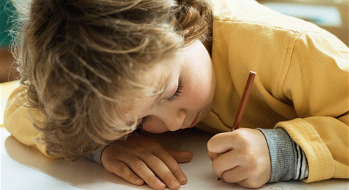 B8PK65 Little girl writing at desk